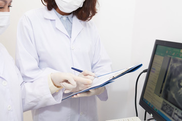 Crop shot of doctor examining panoramic x-ray on computer screen and assistant taking notes on clipboard
