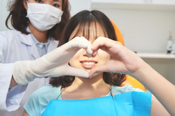 Dentist in glove and young girl in dental chair stacking hands and making heart symbol
