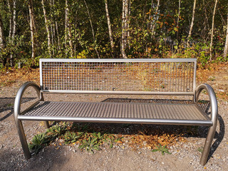 Park bench made of stainless steel in front of a birch forest