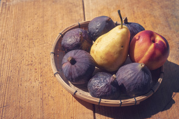 Fruits: figs, pears, peaches on a wooden background
