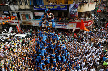 Devotees form a human pyramid to break a clay pot containing curd during the Hindu festival of Janmashtami, marking the birth anniversary of Hindu Lord Krishna, in Mumbai