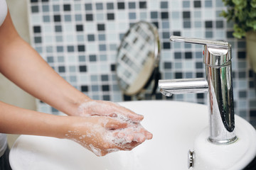 Crop side view of woman washing hands with soapy foam in white sink in bathroom