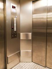 Metal door and wall of a modern elevator cabin