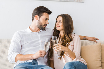 portrait of couple clinking glasses of champagne on sofa at new home