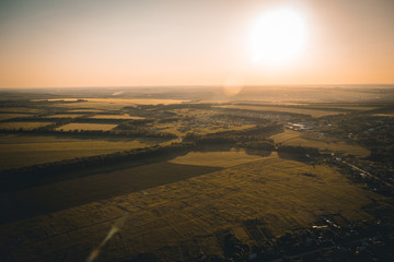 Aerial view from drone to summer rural landscape at sunset sunlight with fields and trees