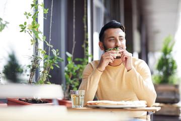 Young man enjoying taste of original Italian pizza while sitting in modern cafe