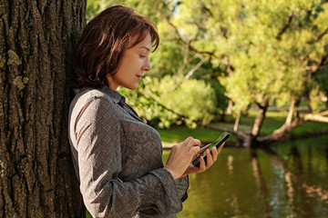 Mature woman with smartphone texting. Woman cell phone