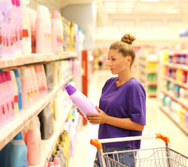 Woman shopping in supermarket reading product information.(washing powder,detergent)