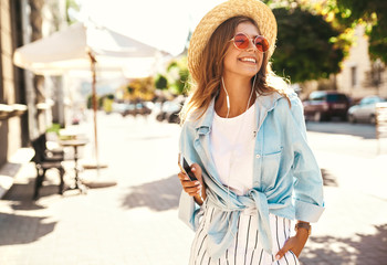 Portrait of beautiful cute smiling blond teenager model in summer hipster clothes walking on the street background and listening music on her mobile phone