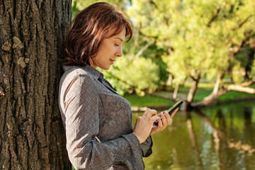 Mature woman with smartphone texting. Mid adult woman outdoors