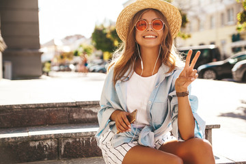 Portrait of beautiful cute blond teenager model in summer hipster clothes sitting on the street background and listening music on her mobile phone. Show peace sign
