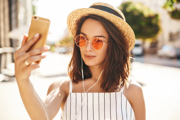 Teen girl in summer white hipster clothes in headphones taking selfie on smartphone on warm sunset background