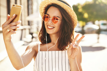 Teen smiling girl in summer white hipster clothes in headphones taking selfie on smartphone on warm sunset background