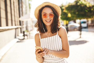 Portrait of happy smiling teen girl in summer hipster clothes listening music on her headphones from smartphone in the street on a sunny day