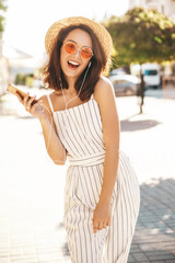 Portrait of happy smiling teen girl in summer hipster clothes listening music on her headphones from smartphone in the street in a summer sunny day