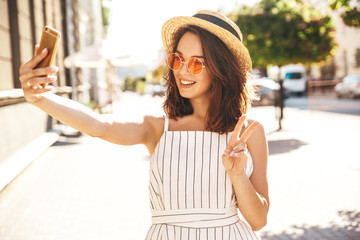 Teen smiling girl in summer white hipster clothes in taking selfie on smartphone on warm sunset background. Showing peace sign