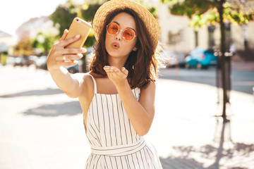 Teen smiling girl in summer white hipster clothes in taking selfie on smartphone on warm sunset background. Giving air kiss