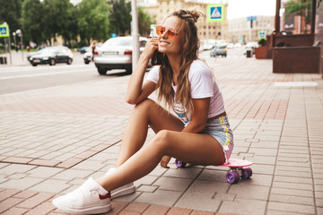 Beautiful young woman in sunglasses drinking colorful cocktail from bottle in the street. Fashionable hairstyle. Lifestyle portrait Fotoväggar