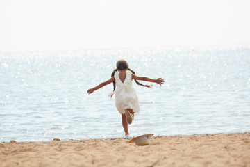 Back view portrait of carefree teenage girl running to sea happily stretching her arms, copy space