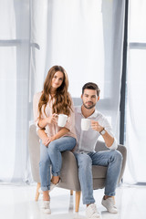 young loving couple with cups of coffee looking at camera at home