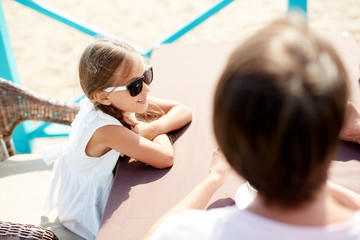 High angle portrait of smiling little girl wearing sunglasses sitting in outdoor cafe with parents enjoying Summer vacation, copy space