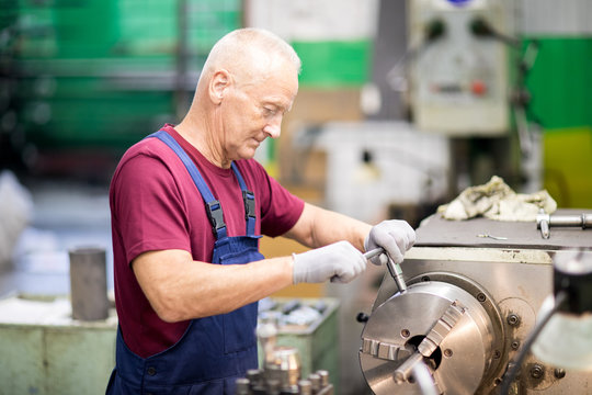 Senior grey-haired worker in uniform and gloves turning circle part of industrial machine