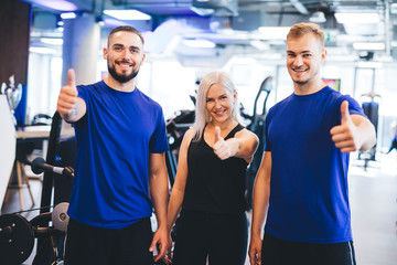 Three happy people at the gym showing thumbs up.