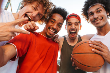 Photo closeup of american sporty men smiling and taking selfie, while playing basketball at playground outdoor during summer sunny day