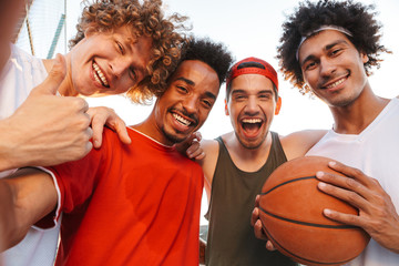 Photo closeup of muscular sporty men smiling and taking selfie, while playing basketball at playground outdoor during summer sunny day