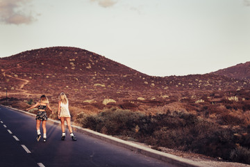 couple of beautiful blonde girls viewed from rear skating and moving on an asphalt road during a sunny day. freedom and rebel alternative vacation concept with young people enjoying the leisure