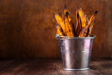 Wall Mural - Homemade baked sweet potato fries in metal serving bucket on wooden background , with copyspace