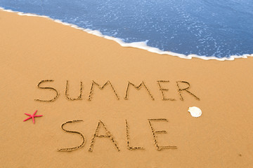 summer sale written in the sand on a sunny beach