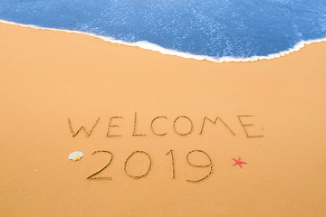 welcome 2019 written in the sand on a beach near the coastline
