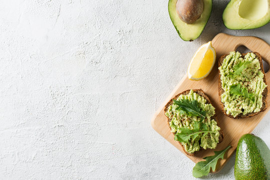 Two toasts with avocado and green salad on breakfast