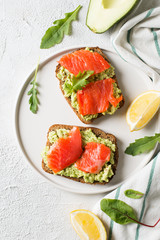 Toasts with avocado and salmon on plate
