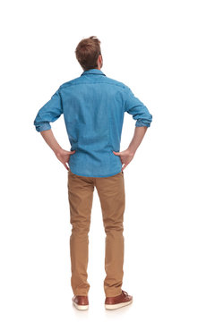 back view of a casual man with hands on waist