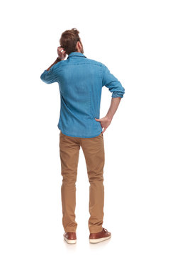 back view of a young casual man scratching his head