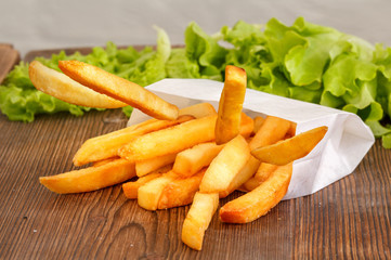 Delicate French fries on a wooden background.