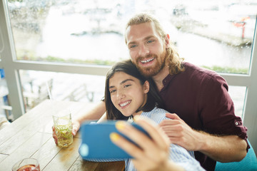Young cheerful couple making selfie while sitting by table in cafe and having drinks
