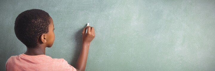 Boy writing with chalk on greenboard in school Wall mural