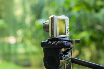 photography equipment of soft focus small cheap gray digital camera stay on tripod in natural unfocused blurred bokeh green outdoor environment with empty space for copy or text