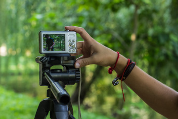 photography hobby and equipment of human hand and fingers on small gray cheap digital camera stay on tripod on unfocused blurred bokeh natural outdoor park environment, copy space