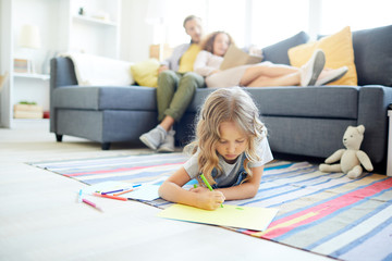 Young parents relaxing on sofa while their little daughter lying on the floor and drawing with crayons