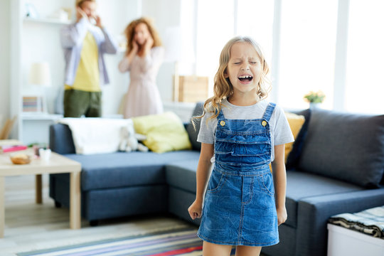 Little girl in casualwear crying and shouting while her parents shutting their ears on background