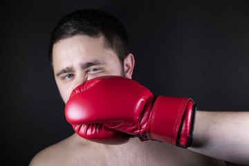 Boxer in red gloves for boxing strikes the opponent to the man. A man with beard is beaten in the face with his fist. Pain from the impact.