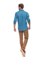 back view of  casual man walking and looking to side