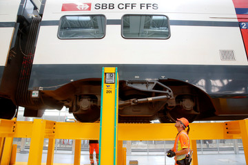 A technician checks a bogie of a train standing on a lifting facility at a maintenance plant of Swiss railway operator SBB in Olten