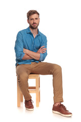 serious young casual man sitting with hands crossed