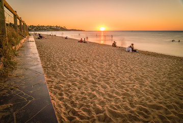People watching the sunset at the beach in Frankston, Australia