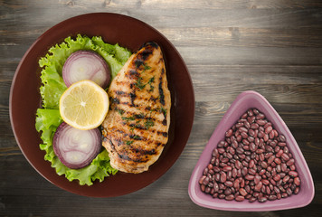 grilled chicken fillet with vegetables (lemon, salad, onion) on a wooden background. chicken fillet grilled on a plate